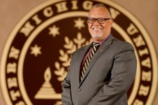 Photo of WMU President Edward Montgomery standing in front of the WMU seal.
