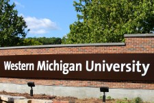 Photo of an outdoor brick and stone sign with trees behind it that reads Western Michigan University.