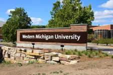 Photo of a brick Western Michigan University sign with rock and landscaping outside and trees.