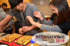 Two international students preparing trays of food.