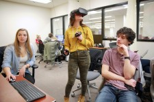 Photo of students sitting at computers and wearing virtual reality gear and controls in a VR lab at Waldo Library.