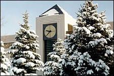 Photo of the WMU library clock tower with pine trees in front that are covered in snow.