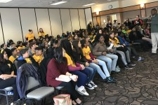 Photo of sixth-graders sitting in chairs and listeneing to a presentation as part of the Bronco BUDS program.