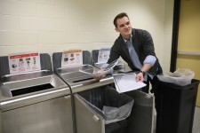 Josh Turske pulls papers out of a recycling bin.