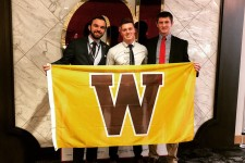 Photo of WMU students Cooper Frost, Ryan Demas and Alex McMahon holding a W flag.