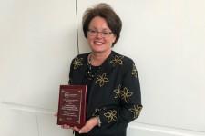 Photo of Tamara Davis holding a plaque.
