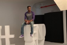 Sam Beal sits on a text statue that reads #END ALZ.