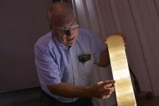 Dr. William Harrison holding a translucent rock core layered with potash.