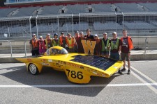 Photo of the 2019 WMU Sunseeker team standing in front of its solar race car on a track.