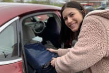Photo of a young woman loading a cooler full of food into the back seat of a car.