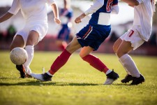 Photo of female soccer players kicking a ball.