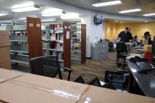 Photo of the renovated Waldo Library service desk area with people moving shelves of books.