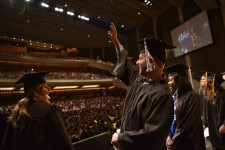 Graduates wave to the audience.