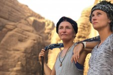 Two young women stand together in the desert looking off into the distance.