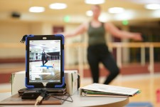 A yoga instructor conducts a class and records it on her ipad.