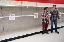 Shoppers stand in front of empty store shelves.