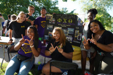 Members of a co-ed business fraternity pose together.