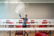 A Custodial Services employee uses misting equipment to disinfect a classroom.