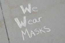 """""""We Wear Masks"""" written in chalk on a sidewalk."""