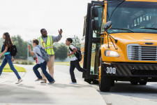 A crossing guard motions for kids getting off of a school bus to cross the street.