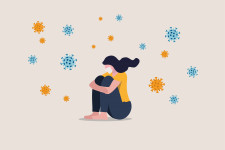 An illustration of a woman sitting with her arms around her knees, surrounded by coronavirus pathogens.