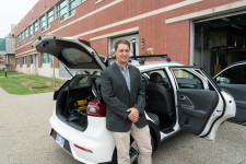 Dr. Zach Asher leans against an SUV that he's outfitted with autonomous technology.