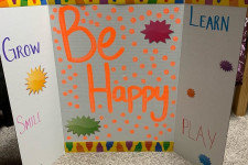 """""""Be Happy"""" is written on a privacy screen."""