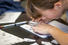 A girl looks at something on a desk closely through a magnifying glass.