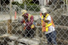 Two construction workers in hardhats behind a fence.
