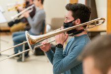 A man in a mask blows into a trombone.