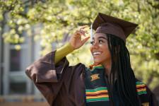 A woman wearing graduation regalia smiles outside on campus.