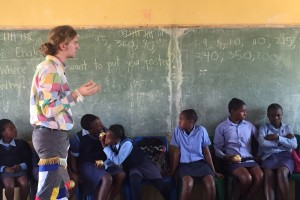 A young man stands at a chalk board teaching a class of South African students.