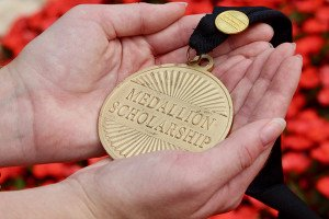Hands holding a Medallion against a red background
