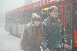 Two students at a snowy bus stop on campus