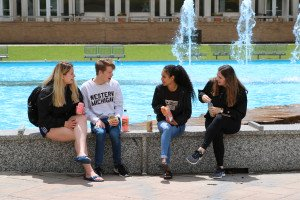 Students sitting by the fountain with snacks