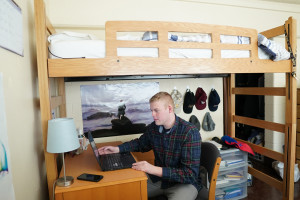 Student in res hall room with lofted bed