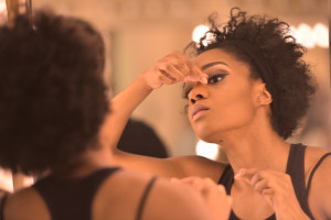 Woman putting on makeup in the mirror before a performance.