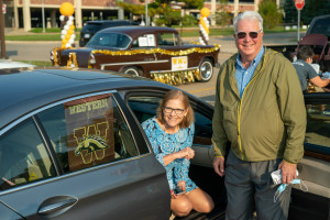 Two people pose next to a car displaying a WMU flag in the window.