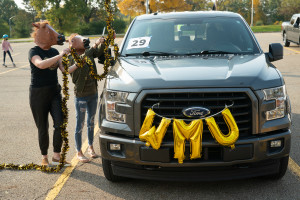 People in horse masks decorate a truck with WMU swag.