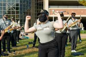 A member of the Bronco Marching Band flexes their muscles.