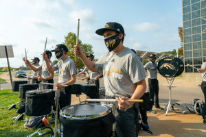 Bronco Marching Band members play the drums.
