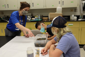 A Western student helps school-aged campers in a classroom.