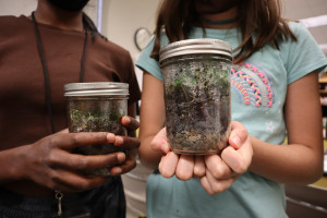 Students hold terrariums.