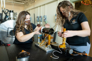 Margaret Mooney and Kristina Lemmer work on a device in a laboratory.