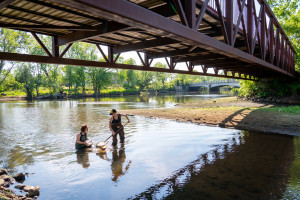 Students stand under a bridge in the Kalamazoo river.