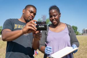 Students look at water samples.
