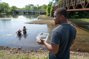Jovaughn Carver holds a container of water next to a river.