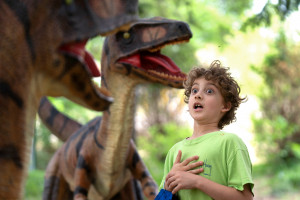 A young boy gasps in front of menacing utahraptor statues.