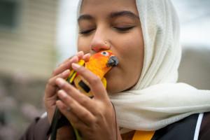 Aisha Thaj gives her pet bird a kiss.
