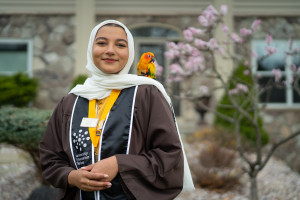 Aisha Thaj poses with her pet bird on her shoulder.